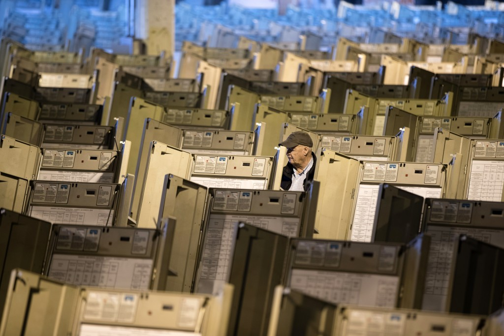 FILE- In this Oct. 14, 2016, file photo, a technician works to prepare voting machines to be used in the upcoming presidential election, in Philadelph