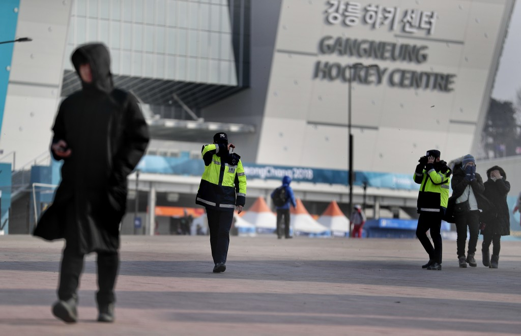 Police officers shield their faces from strong winds as they help clear the park of spectators at Gangneung Olympic Park at the 2018 Winter Olympics i
