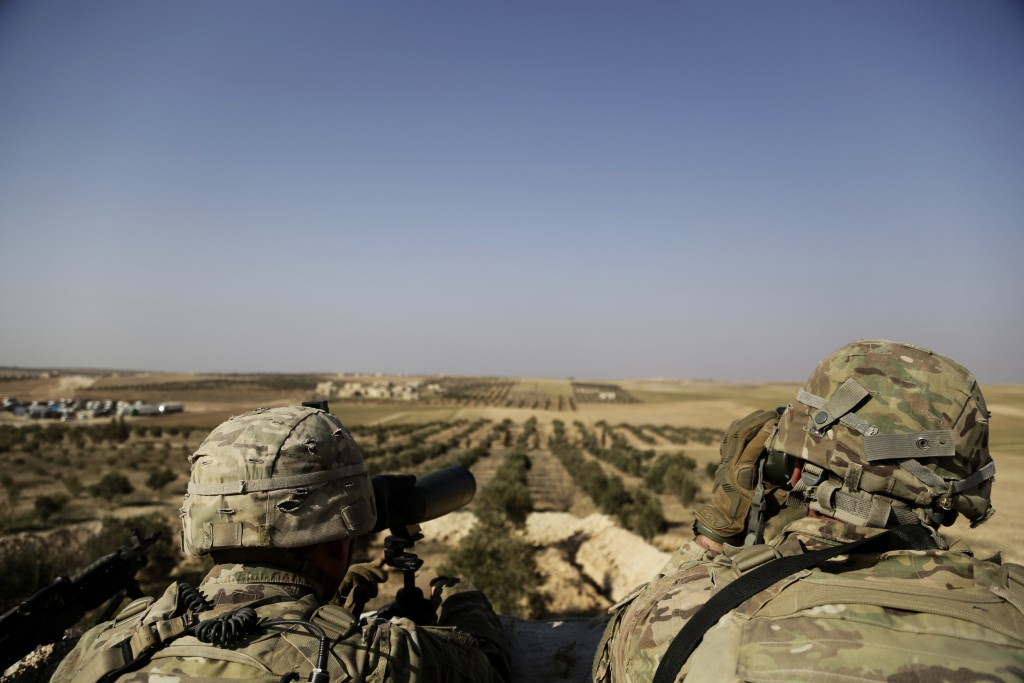 FILE - This Wednesday, Feb. 7, 2018 file photo, shows American troops looking  toward the border with Turkey from a small outpost near the town of Man