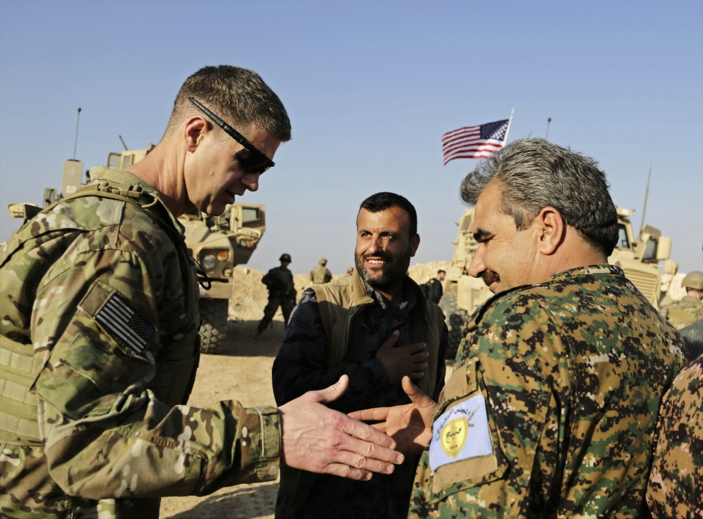 FILE - This Wednesday, Feb. 7, 2018 file photo, shows U.S. Army Maj. Gen. Jamie Jarrard left, thanks Manbij Military Council commander Muhammed Abu Ad