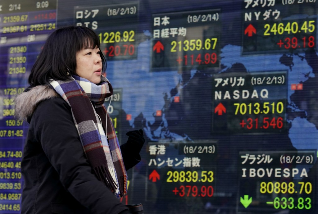 A woman walks past an electronic stock indicator of a securities firm in Tokyo, Wednesday, Feb. 14, 2018. Asian shares were mixed Wednesday amid a wai