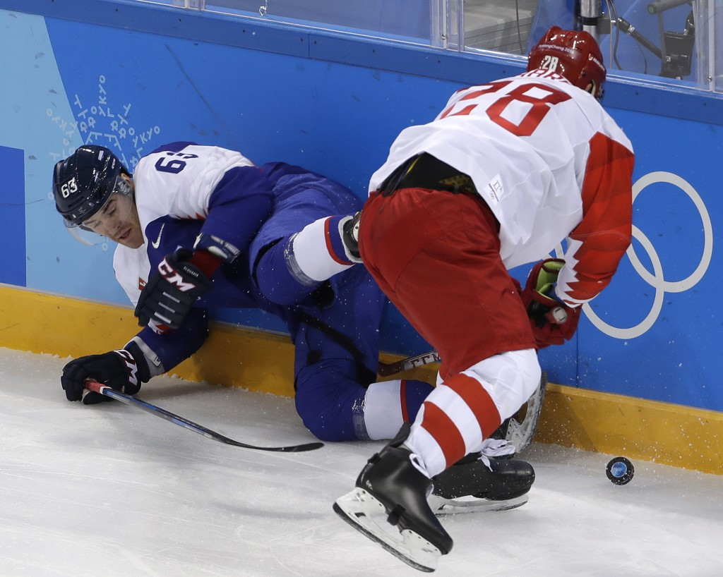 Patrik Lamper (63), of Slovakia, falls as he battles for the puck against Russian athlete Andrei Zubarev (28) during the first period of the prelimina