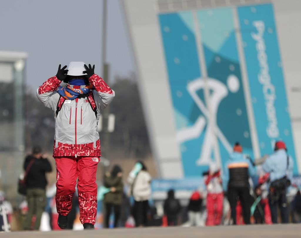A volunteer peeks under its hood while walking against gusty winds at the Olympic Park at the 2018 Winter Olympics in Gangneung, South Korea, Wednesda