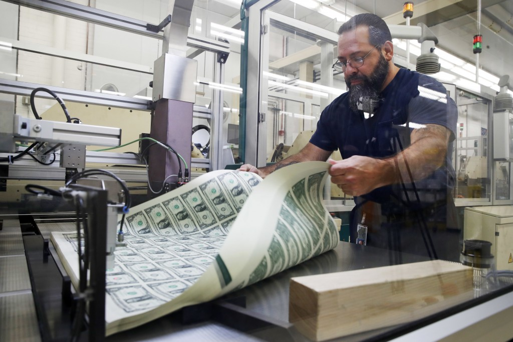 FILE- In this Nov. 15, 2017, file photo, Vincent Tacconelli aerates printed sheets of dollar bills, the first currency notes to bear the signatures of