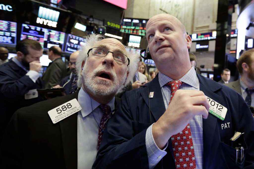 FILE- In this Thursday, Feb. 8, 2018, file photo, traders Peter Tuchman, left, and Patrick Casey work on the floor of the New York Stock Exchange. The