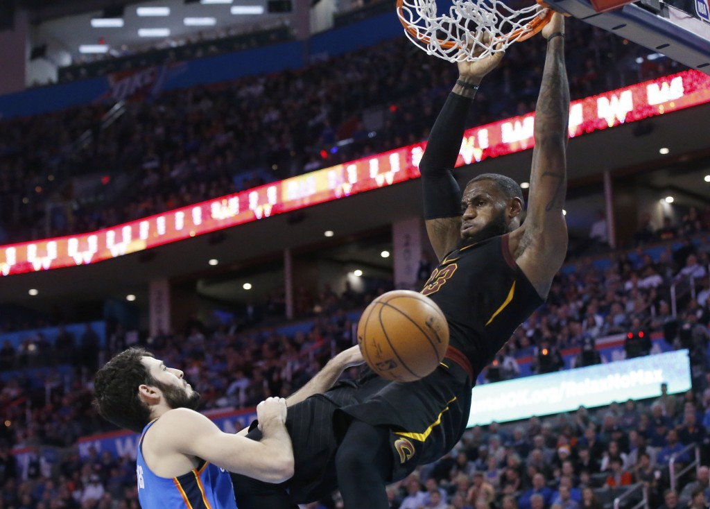 Cleveland Cavaliers forward LeBron James hangs from the basket after dunking in front of Oklahoma City Thunder guard Alex Abrines during the first hal