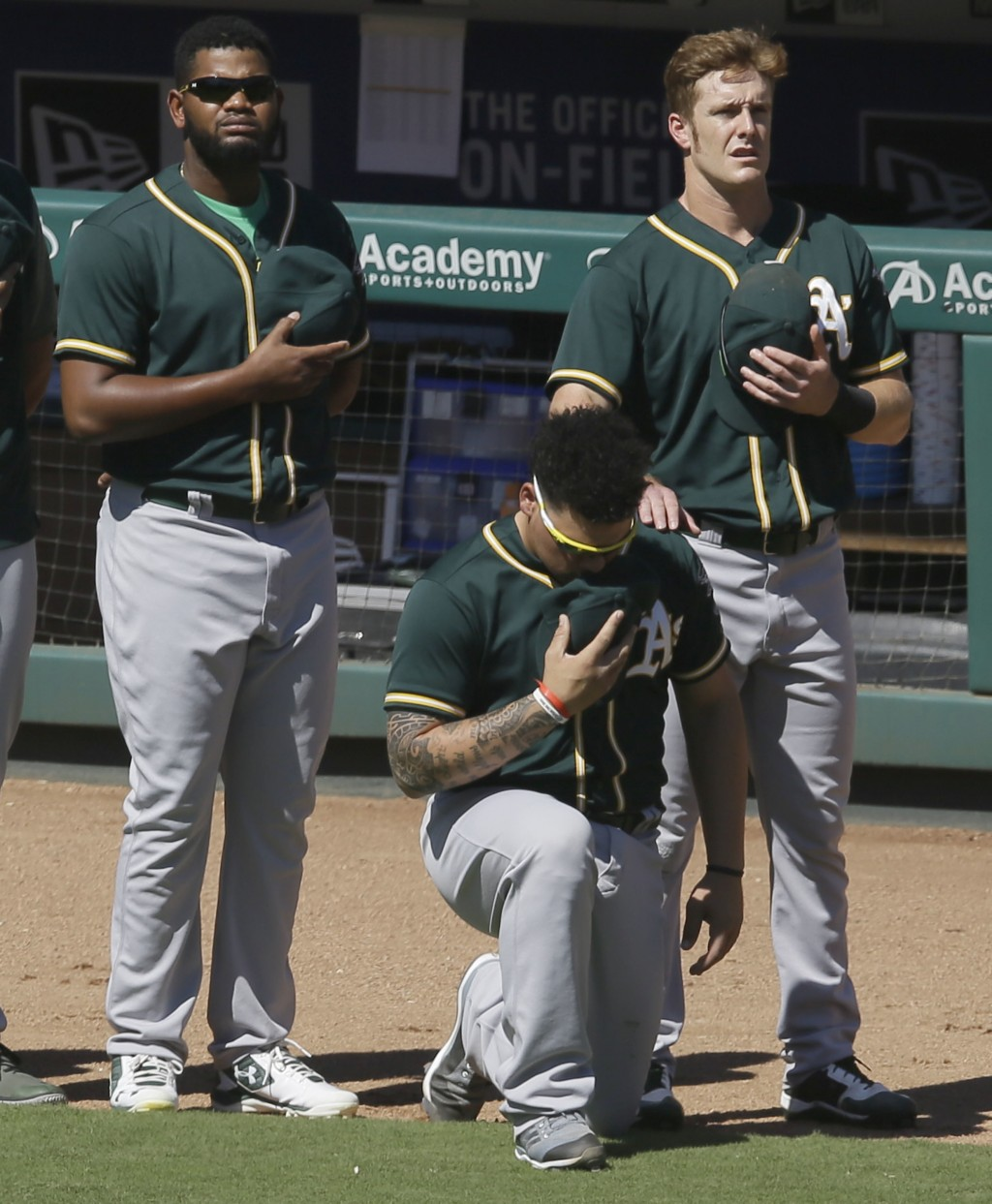 FILE - In this Sunday, Oct. 1, 2017 file photo, Oakland Athletics catcher Bruce Maxwell takes a knee during the national anthem next to teammates Mark
