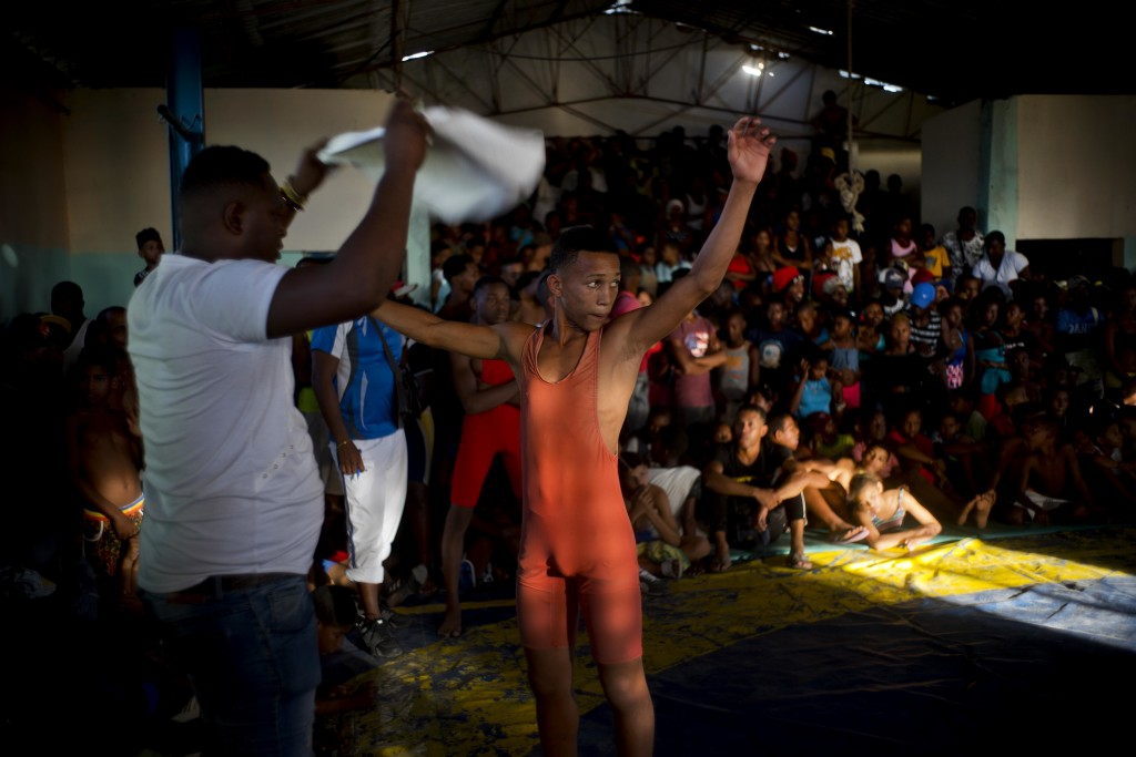 """In this Jan. 23, 2018 photo, a young wrestler is fanned off with a towel by his coach during the week-long student wrestling championship coined """"The"""