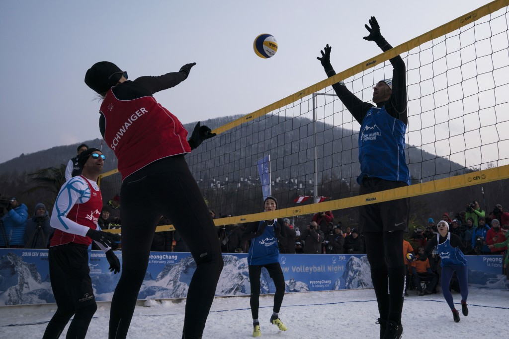 Brazil's Giba, right, tries to block Austria's Stefanie Schwaiger during a snow volleyball exhibition match at the Austria House in Pyeongchang, South