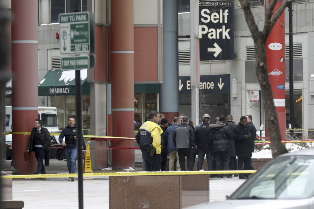 Police gather at the scene where an off-duty officer was shot while assisting a tactical team at a state government office building, Tuesday, Feb. 13,
