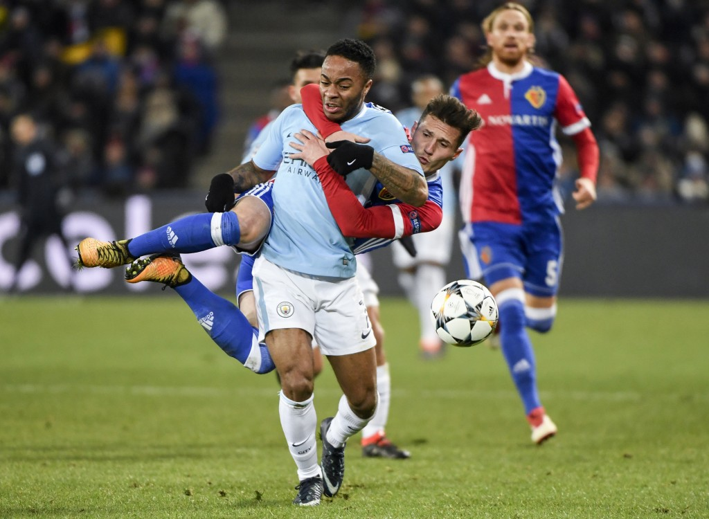 Basel's Taulant Xhaka, behind, clings to Manchester City's Raheem Sterling, front, and gets a yellow card for this action, during the UEFA Champions L