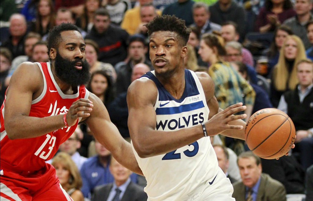 Minnesota Timberwolves' Jimmy Butler (23) drives on Houston Rockets guard James Harden (13) during the second quarter of an NBA basketball game Tuesda