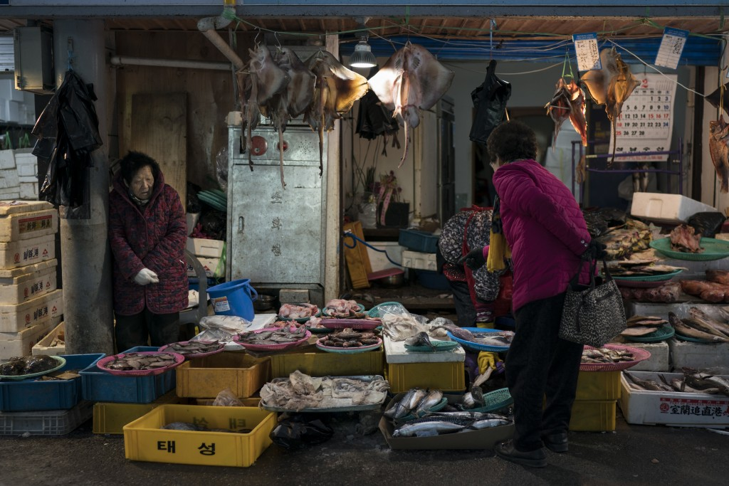 A woman shops for fish at the traditional market in Gangneung, South Korea, Tuesday, Feb. 13, 2018. While the Winter Olympics are going on in the moun