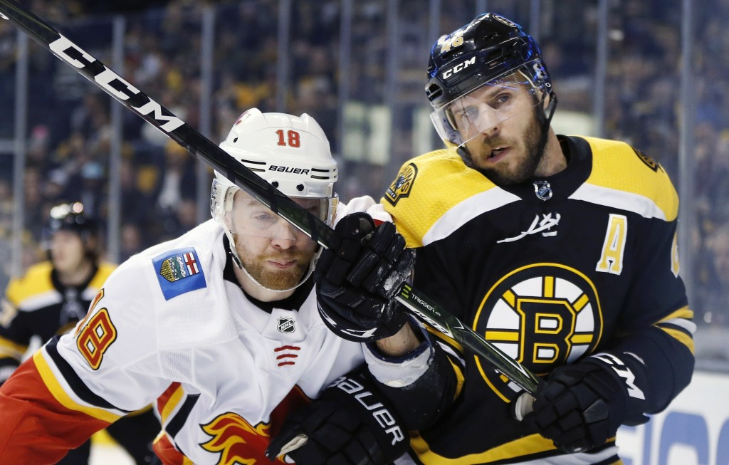 Calgary Flames' Matt Stajan (18) checks Boston Bruins' David Krejci (46), of the Czech Republic, during the first period of an NHL hockey game in Bost