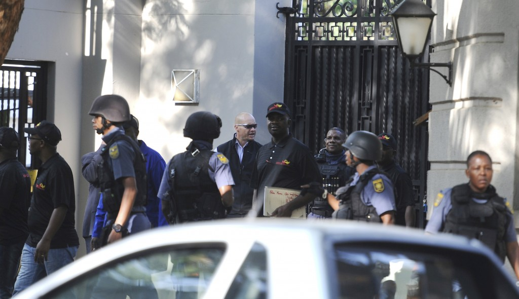 South African police exit after a raid on a home in Johannesburg, Wednesday, Feb. 14, 2018. The police raided the home of a business family linked to
