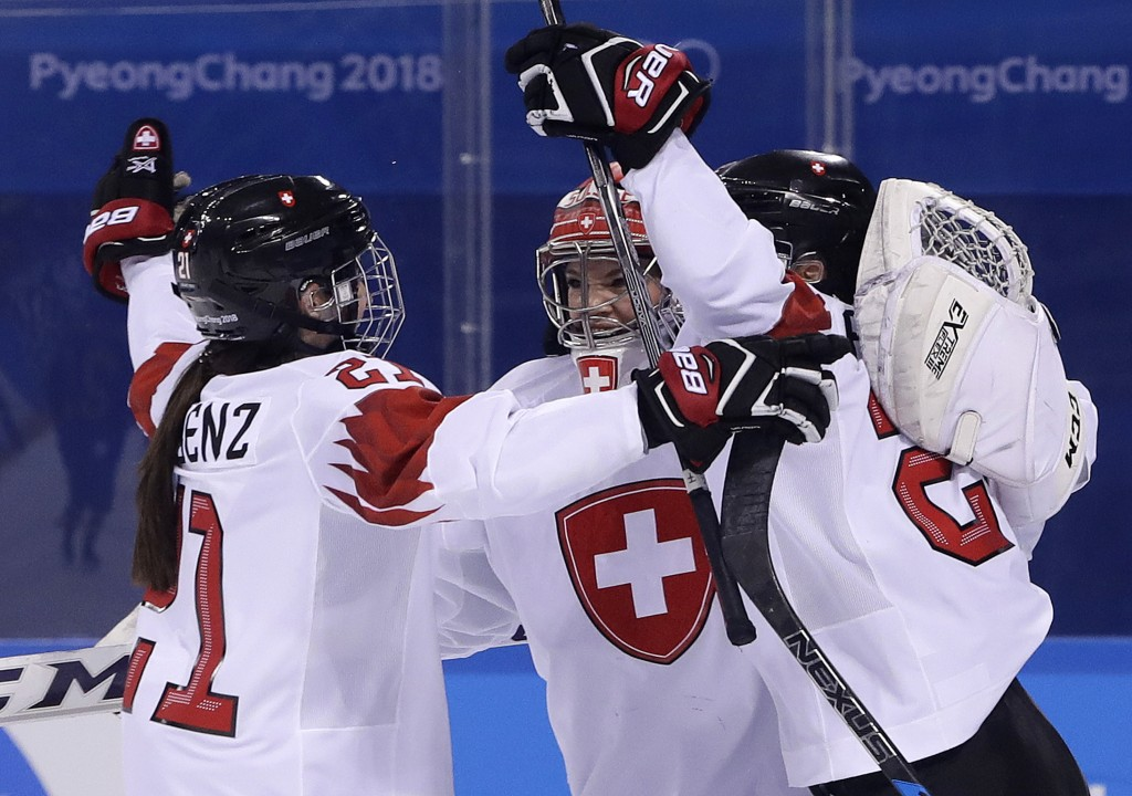 Laura Benz (21), goalie Florence Schelling (41) and Livia Altmann (22), of Switzerland, celebrate after the preliminary round of the women's hockey ga