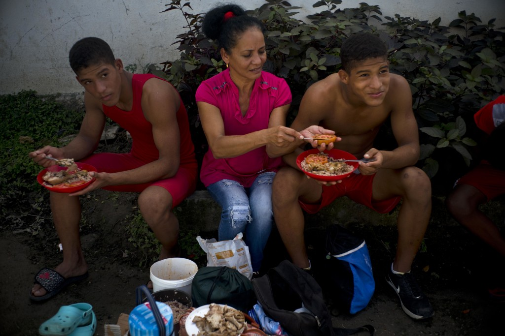 """In this Jan. 23, 2018 photo, Nalis Mendoza slices a tomato as she feeds her sons attending the week-long student wrestling championship coined """"The tr"""