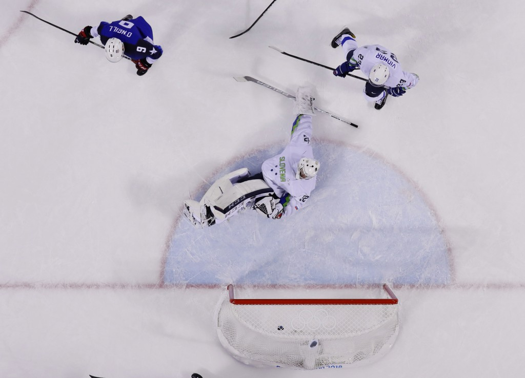 Brian O'Neill (9), of the United States, watches goaltender Gasper Kroselj (32) , of Slovenia, react after shooting a puck past for a goal as teammate