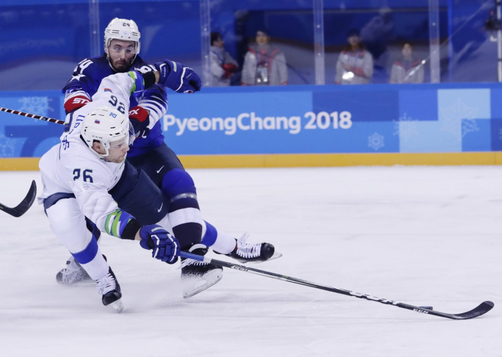 Jonathon Blum (24), of the United States, defends Jan Urbas (26), of Slovenia, during the first period of the preliminary round of the men's hockey ga