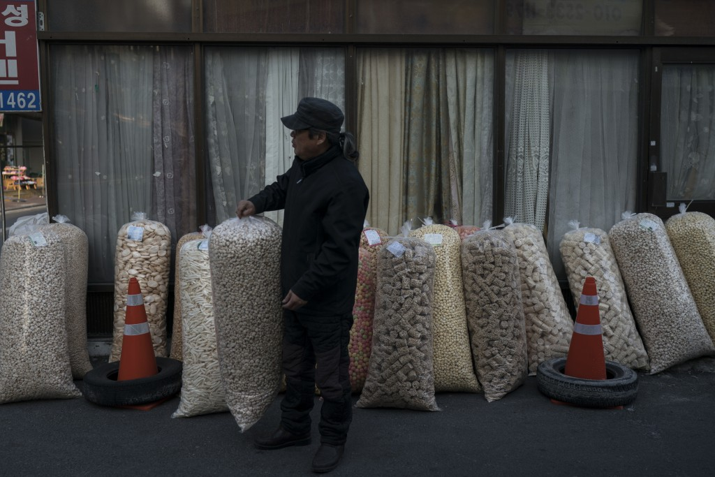 A man sells large bags of popped grains at the traditional market in Gangneung, South Korea, Tuesday, Feb. 13, 2018. Markets like this one are a commo