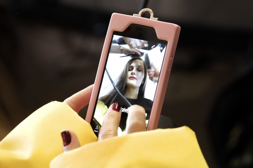 A model records her hair styling on her mobile phone backstage before the Badgley Mischka collection is modeled during Fashion Week in New York, Tuesd