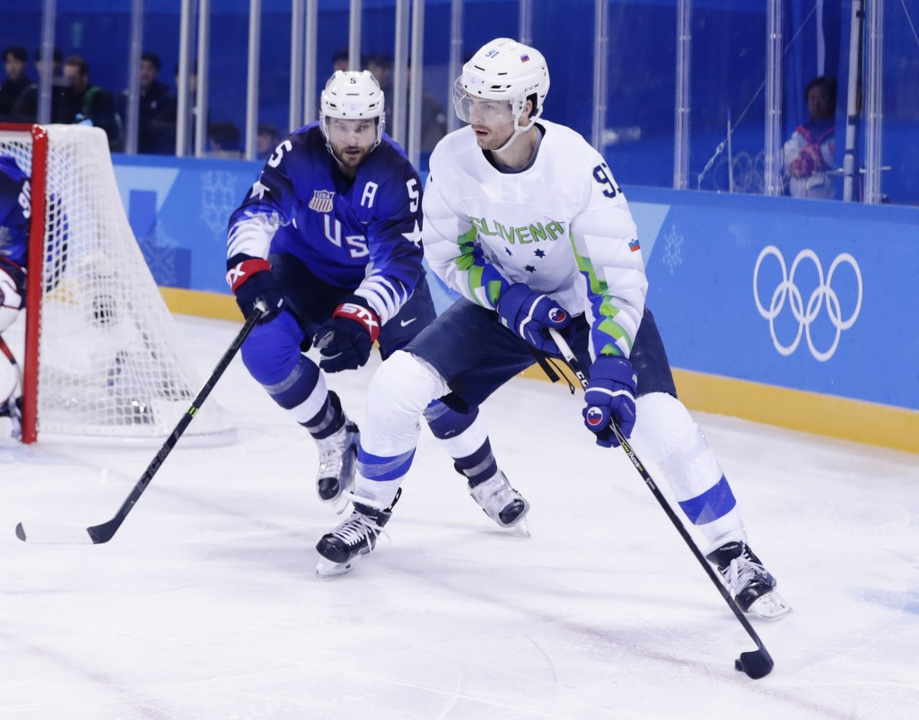 Noah Welch (5), of the United States, defends Miha Verlic (91), of Slovenia, during the first period of the preliminary round of the men's hockey game