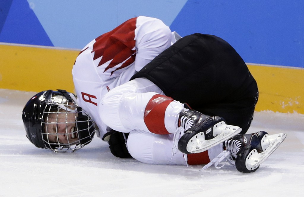 Lara Stalder (7), of Switzerland, grimaces in pain during the third period of the preliminary round of the women's hockey game against Sweden at the 2