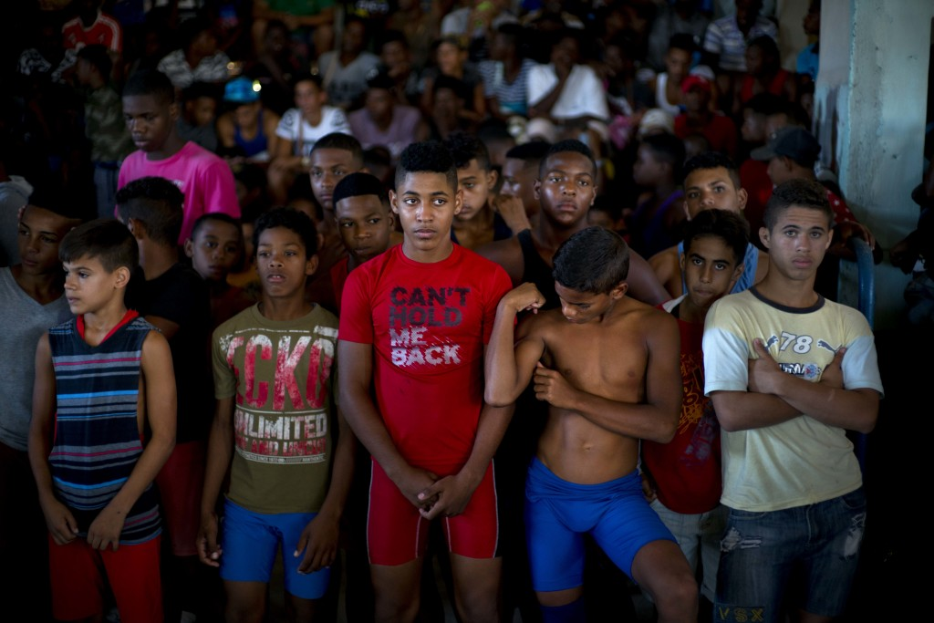 In this Jan. 23, 2018 photo, young wrestlers stand still during a priest's prayer at the start of the week-long student wrestling championship coined