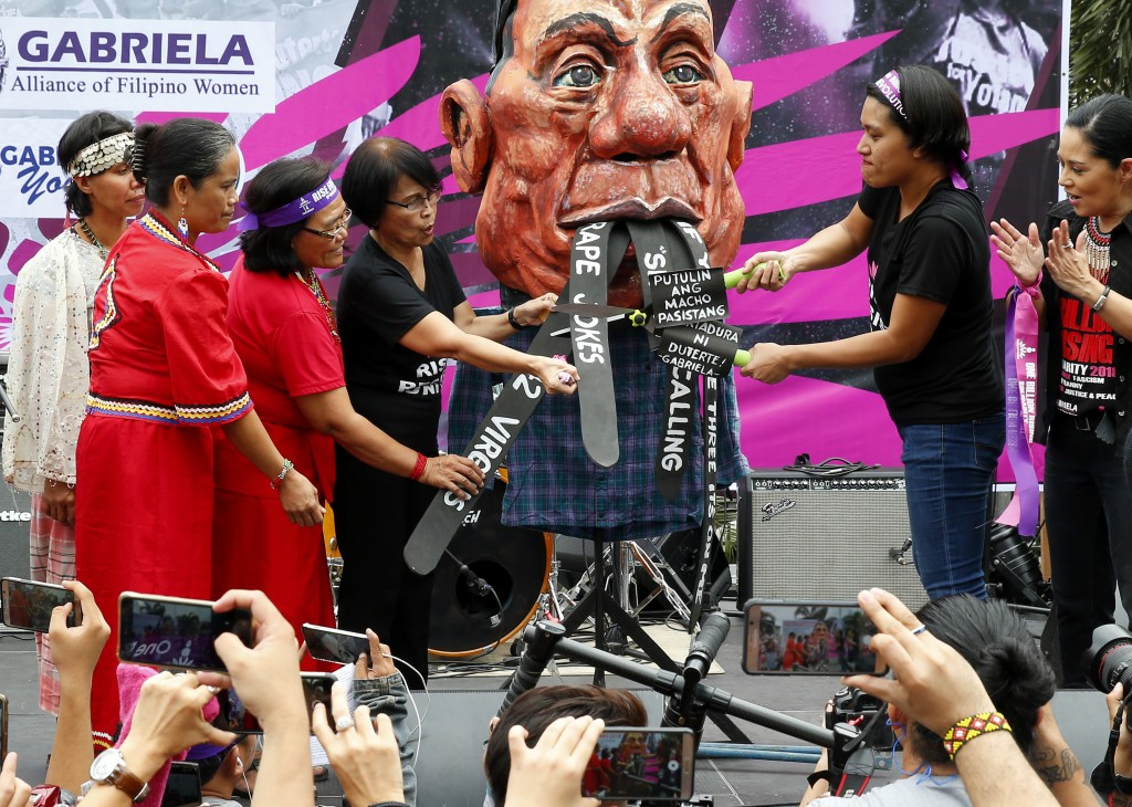 """Protesters cut President Rodrigo Duterte's """"tongues"""" which allegedly represent his often derogatory statements towards women during a Valentine's Day ..."""