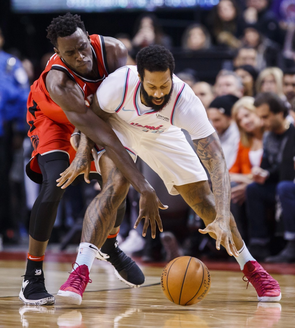 Toronto Raptors' forward Pascal Siakam reaches around Miami Heat forward James Johnson, right, during the first half of an NBA basketball game, Tuesda