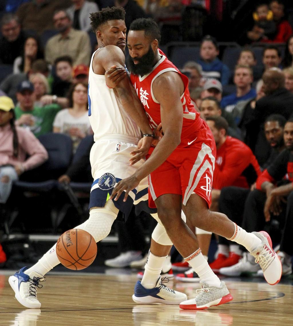 Minnesota Timberwolves forward Jimmy Butler, left, defends against Houston Rockets guard James Harden during the first quarter of an NBA basketball ga