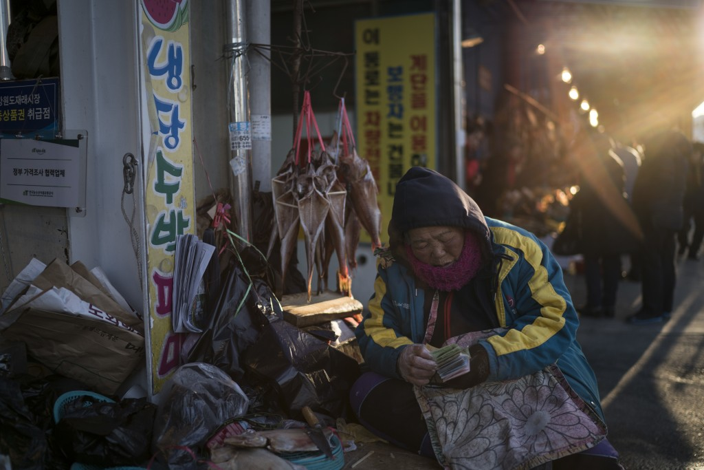 A woman selling fish waits for customers at a market in Gangneung, South Korea, Monday, Feb. 12, 2018. One part of the Pyeongchang area that hasn't be
