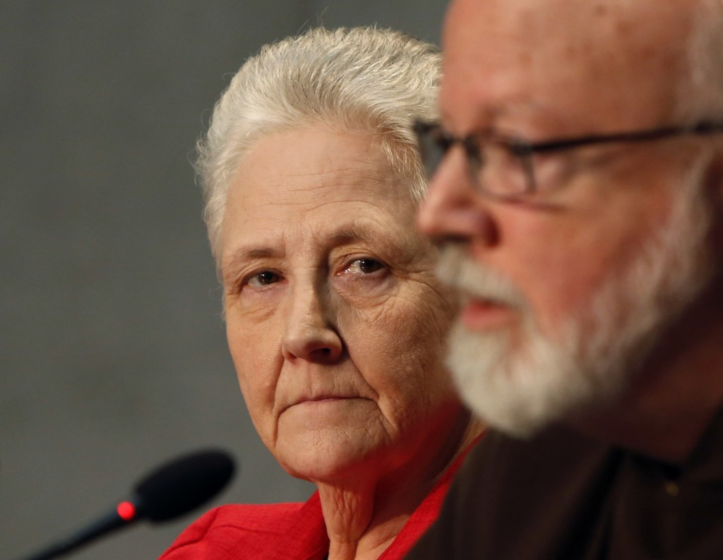 FILE - In this May 3, 2014 file photo, member of the pope's sex abuse commission, Marie Collins, listens to Cardinal Sean O'Malley, the archbishop of