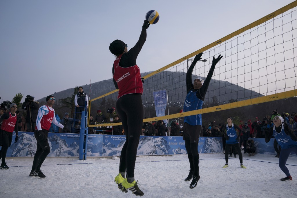 Brazil's Giba, center right, tries to block Austria's Stefanie Schwaiger during a snow volleyball exhibition match at the Austria House in Pyeongchang