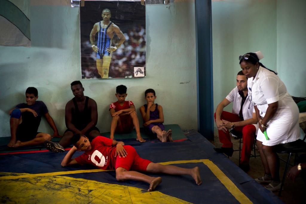 In this Jan. 23, 2018 photo, volunteer nurse Elena Bandera Silega and Doctor Felix Ame Perez sit on the sidelines of the week-long student wrestling c
