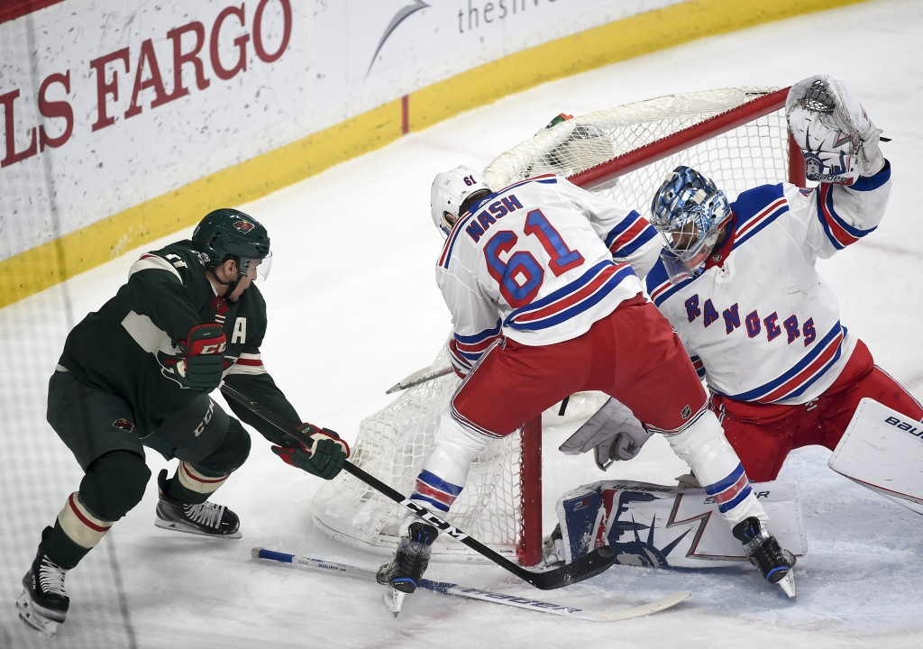 Minnesota Wild left wing Zach Parise, left, pushes the puck past New York Rangers left wing Rick Nash (61) and goalie Henrik Lundqvist, of Sweden, to