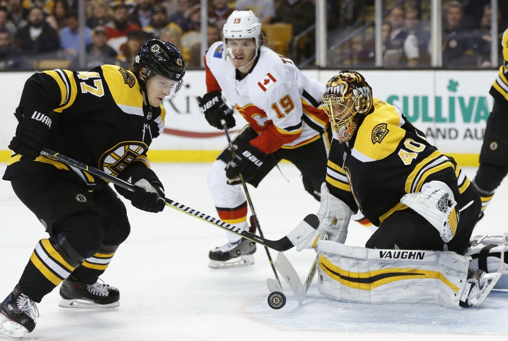 Boston Bruins' Torey Krug (47) moves to clear the puck after a shot by Calgary Flames' Matthew Tkachuk (19) on Tuukka Rask (40), of Finland, during th