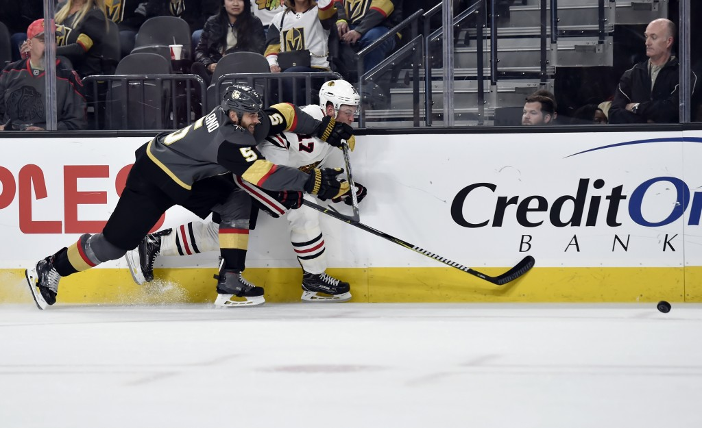Vegas Golden Knights defenseman Deryk Engelland (5) and Chicago Blackhawks left wing Lance Bouma chase down the puck during the first period of an NHL