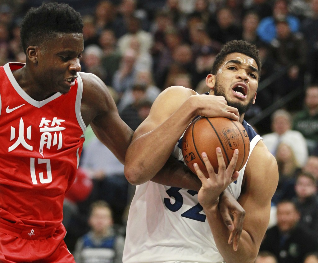 Minnesota Timberwolves forward Karl-Anthony Towns (32) pulls in a rebound against Houston Rockets Clint Capela during the first quarter of an NBA bask