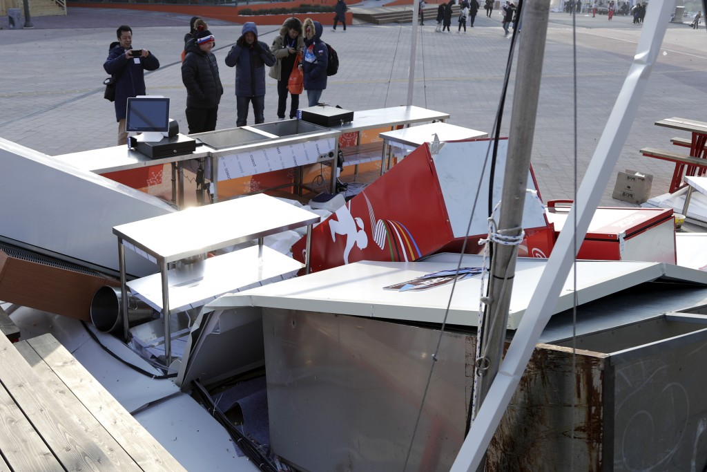 People look at a concession stand blown by gusty winds at the Olympic Park at the 2018 Winter Olympics in Gangneung, South Korea, Wednesday, Feb. 14,