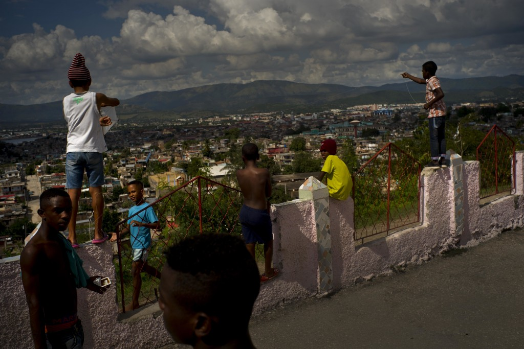 In this Jan. 23, 2018 photo, young wrestlers from Cuba's eastern and central provinces take a break near local kids flying kites, during the week-long