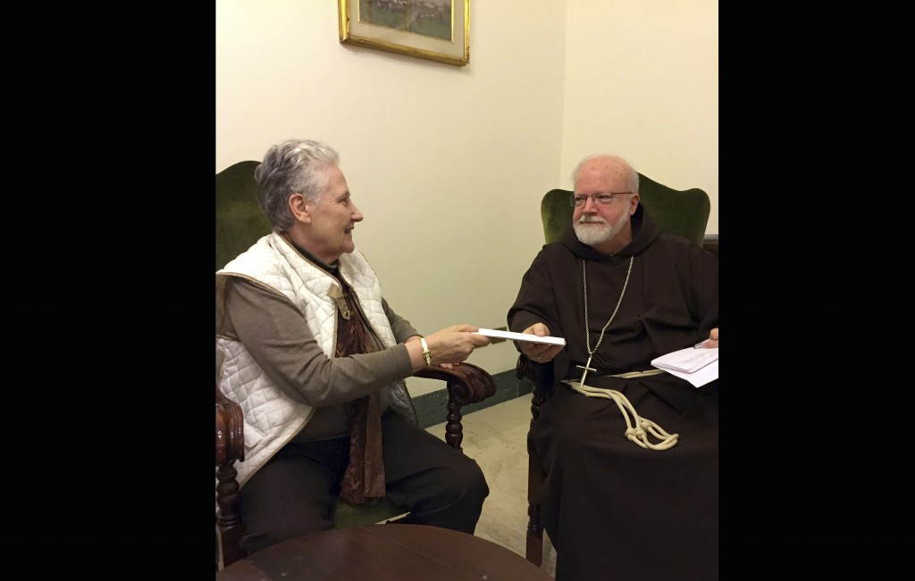 FILE - This Feb. 3, 2018 file photo shows Marie Collins, a member of the Pope Francis' sex-abuse commission, handing a letter to Cardinal Sean O'Malle