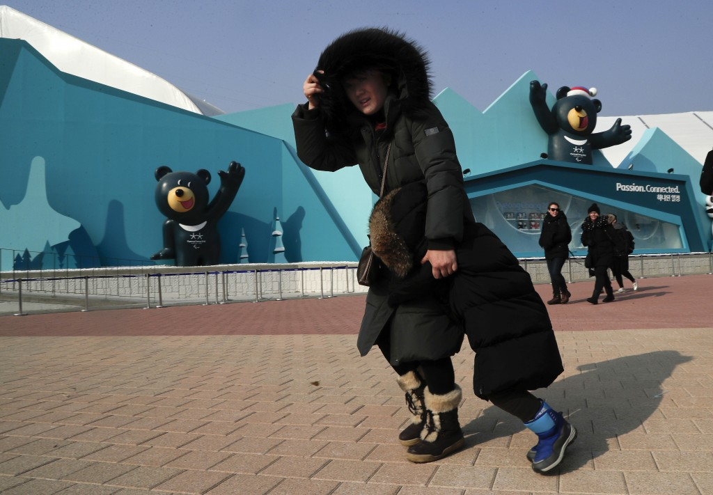 A woman shields her face and a child from gusty winds that whipped through Gangneung Olympic Park at the 2018 Winter Olympics in Gangneung, South Kore