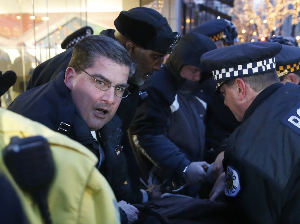 In this Feb. 23, 2016 photo, then Chicago police Capt. Paul Bauer, left, takes part in the arrest of a protester outside an Apple store on Magnificent