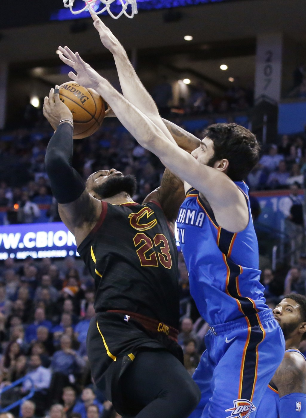 Cleveland Cavaliers forward LeBron James, left, is fouled by Oklahoma City Thunder guard Alex Abrines as he shoots during the first half of an NBA bas