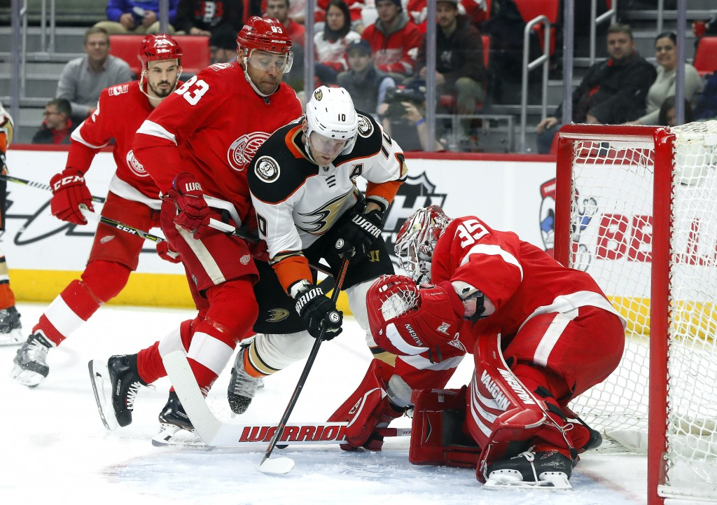 Detroit Red Wings goaltender Jimmy Howard (35) stops a Anaheim Ducks' Corey Perry (10) shot as Trevor Daley (83) defends in the first period of an NHL