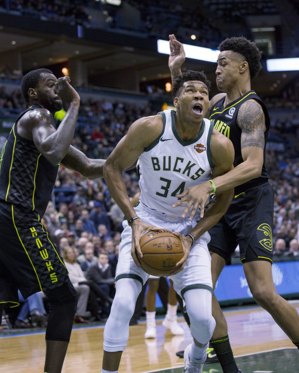 Milwaukee Bucks forward Giannis Antetokounmpo, center, is defended by Atlanta Hawks guard Kent Bazemore, left, and John Collins, right, during the fir