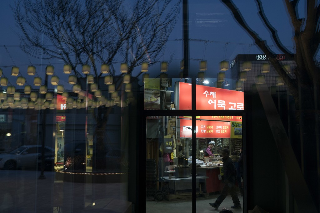 Decorative lamps are reflected on a glass door as a man walks past a restaurant at the traditional market in Gangneung, South Korea, Tuesday, Feb. 13,