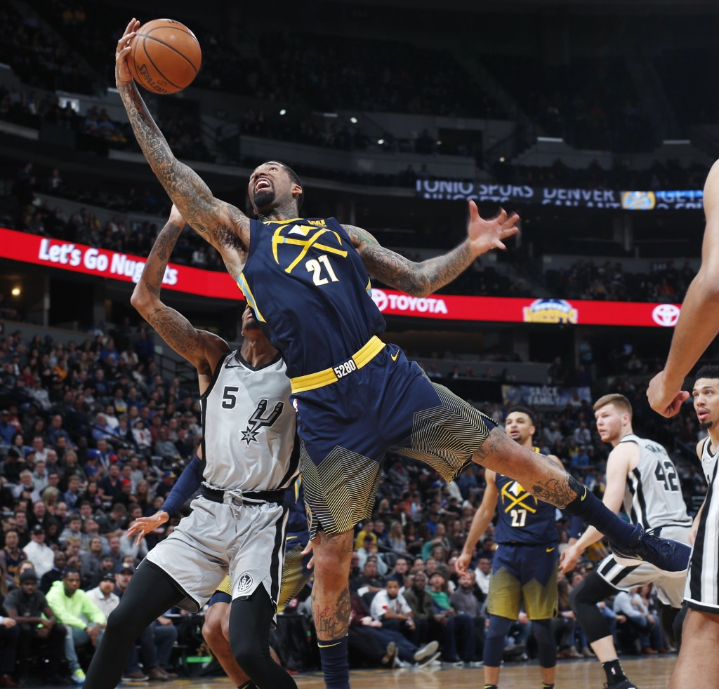Denver Nuggets forward Wilson Chandler, front, reaches over San Antonio Spurs guard Dejounte Murray for the ball during the first half of an NBA baske