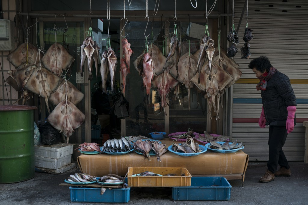 A vendor stands next to dried rays and other fish displayed for sale at the traditional market in Gangneung, South Korea, Tuesday, Feb. 13, 2018. One